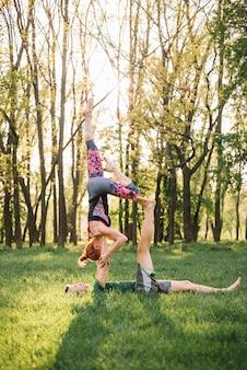 Casal caucasiano saudável praticando ioga no campo gramado