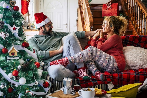 Casal caucasiano se divertindo enquanto está sentado no sofá da sala durante a celebração do natal em casa. casal de chapéu e meias com árvore de natal decorada.