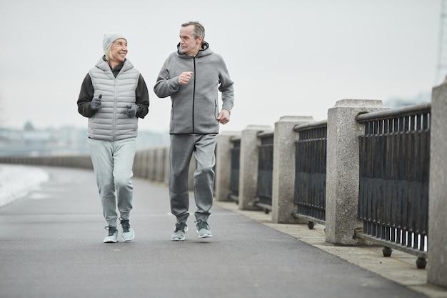 Casal caucasiano sênior positivo de corredores com roupas quentes, correndo ao longo da margem do rio com grades de metal e conversando um com o outro