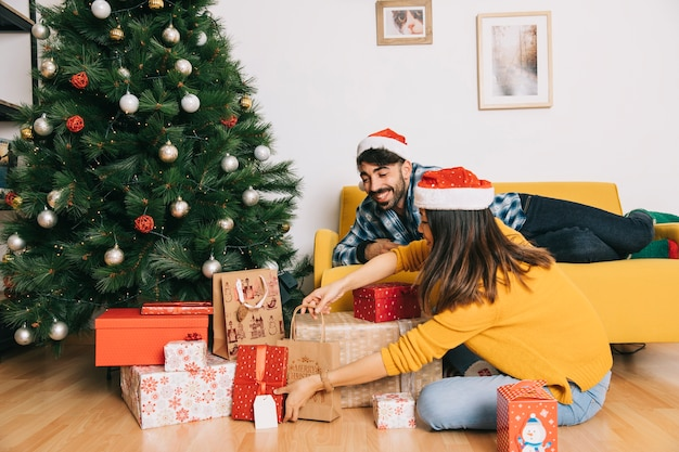 Casal celebrando natal na sala de estar