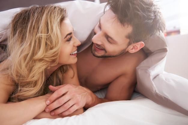 Casal charmoso coberto com edredom