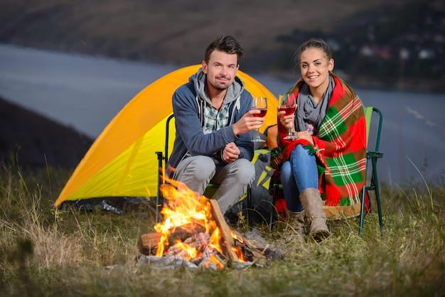 Casal charmoso perto de um fogo enquanto acampar bebendo vinho