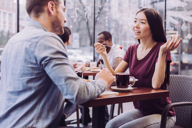 Casal charmoso satisfeito sentado em um café e uma linda mulher gesticulando enquanto carregava o garfo
