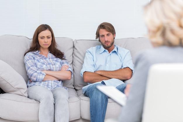 Casal chateado sentar em um sofá com os braços cruzados