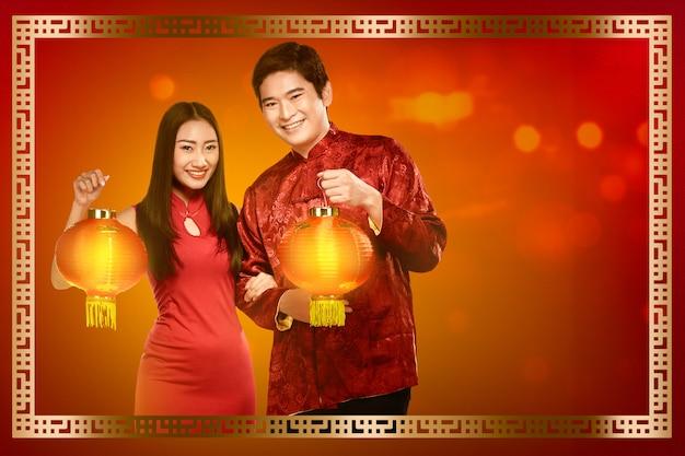 Casal chinês alegre no vestido tradicional segurando lanternas vermelhas