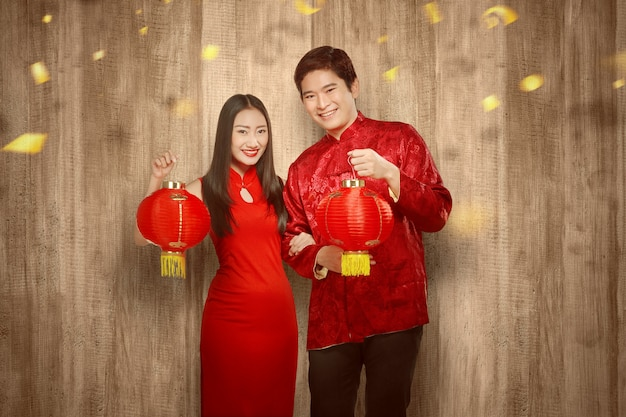 Casal chinês asiático no vestido cheongsam segurando lanterna chinesa