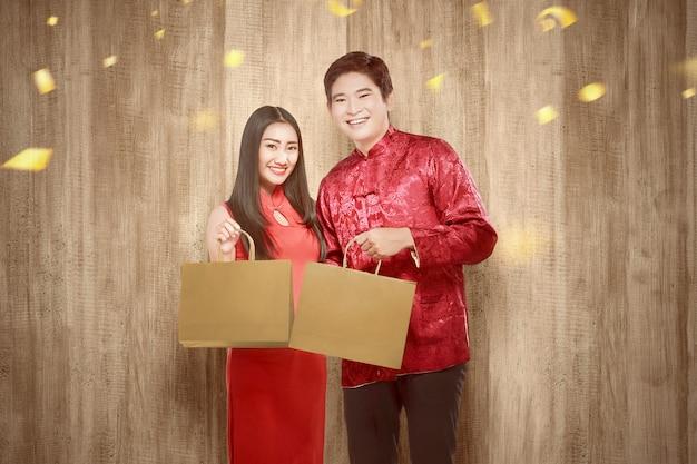 Casal chinês asiático no vestido cheongsam segurando sacolas de compras