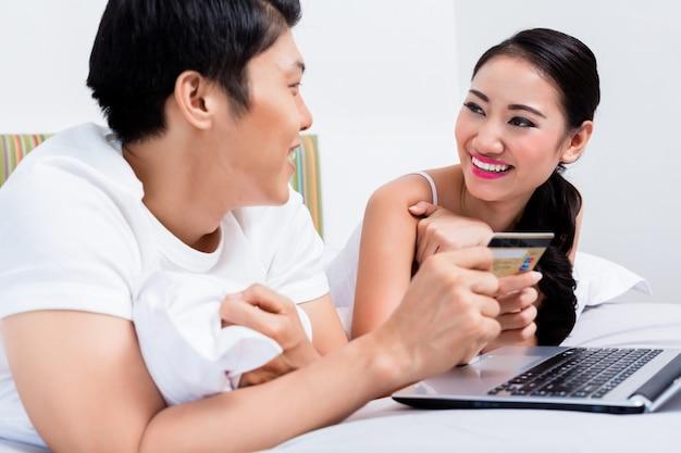Casal chinês de compras on-line de seu quarto