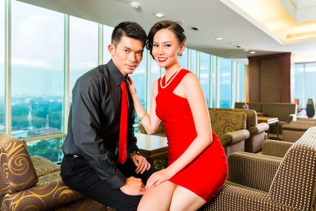 Casal chinês flertando em um bar de hotel de céu de luxo