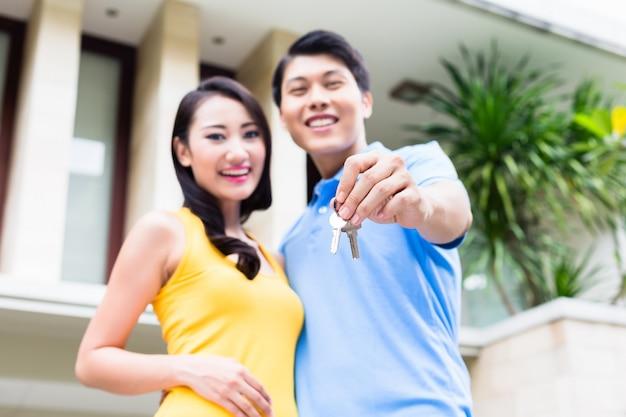 Casal chinês mostrando as chaves para sua nova casa