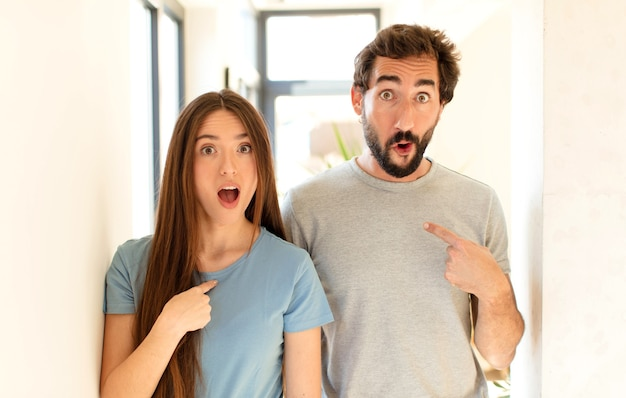 Casal chocado e surpreso com a boca bem aberta, apontando para si mesmo
