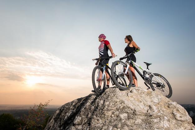 Casal ciclista, homem e mulher, com bicicletas de montanha ao pôr do sol