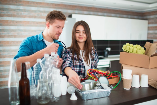 Casal classifica lixo na cozinha. os resíduos devem ser enviados para reciclagem. existem muitos materiais recicláveis. sobre a mesa estão plásticos, vidro, ferro, papel, aparelhos elétricos antigos e resíduos biodegradáveis.