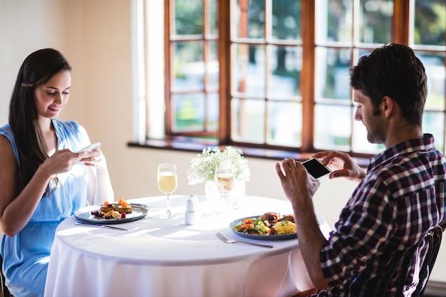 Casal, clicando em foto de um alimento no prato