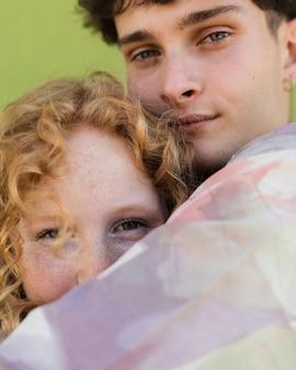 Casal close-up, abraçando com fundo verde