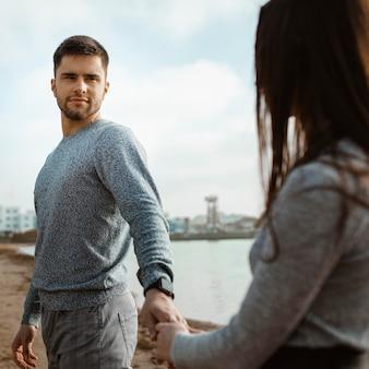 Casal close-up de mãos dadas na praia