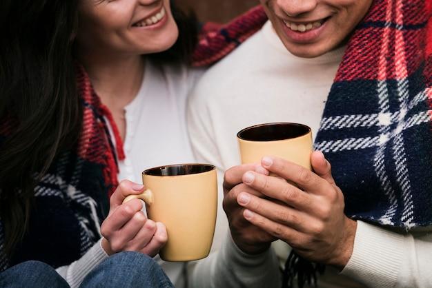 Casal close-up segurando bebidas quentes