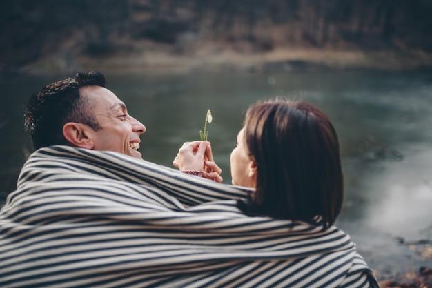Casal coberto com cobertor sentado à beira do lago