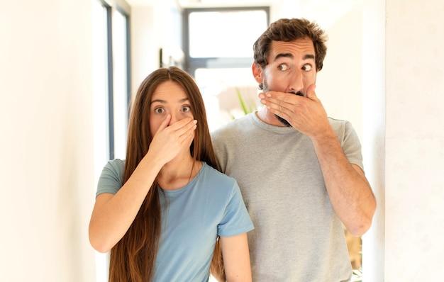 Casal cobrindo a boca com as mãos com uma expressão chocada e surpresa, mantendo um segredo ou dizendo oops