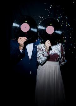 Casal cobrindo rostos com discos de vinil na festa