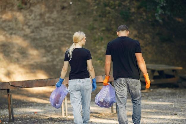 Casal coleta lixo em sacos de lixo no parque