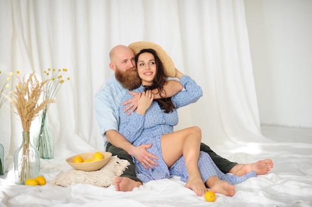 Casal com a mulher de chapéu sentada no chão com limões e um fundo de cortina branca.