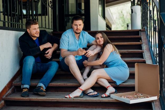 Casal com amigo sentado nos degraus da casa