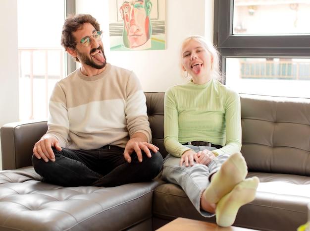 Casal com atitude alegre, despreocupada, rebelde, brincando e mostrando a língua, se divertindo