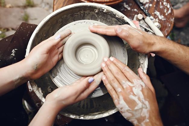 Casal com aventais marrons fazendo um vaso