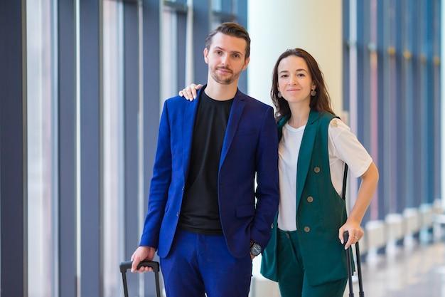 Casal com bagagem no aeroporto internacional, correndo para um voo para aterrar. homem e mulher olhando no relógio interior perto de grande janela