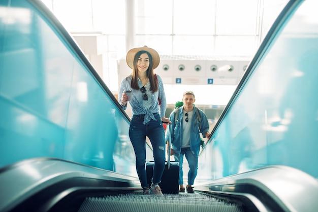Casal com bagagem sobe a escada rolante no aeroporto. passageiros com bagagem no terminal aéreo