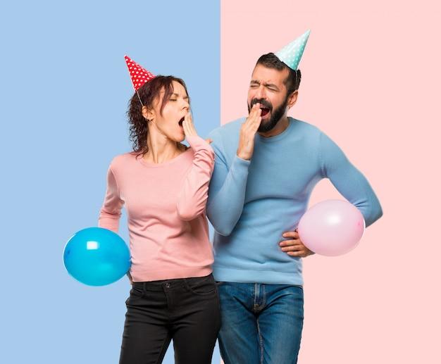 Casal com balões e chapéus de aniversário, bocejando e cobrindo a boca com a mão.