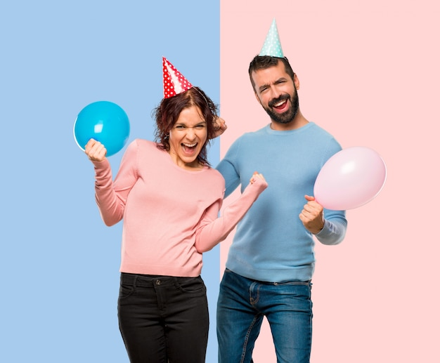 Casal com balões e chapéus de aniversário comemorando uma vitória e feliz por ter ganhado um pr