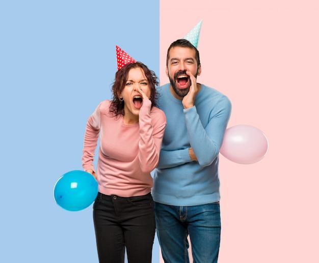 Casal com balões e chapéus de aniversário gritando com a boca aberta e anunciando algo