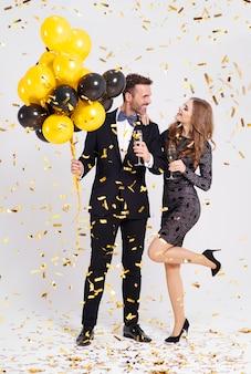Casal com balões e taça de champanhe comemorando o ano novo