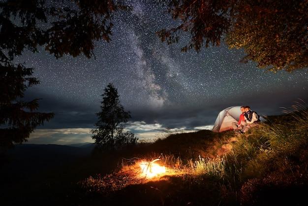 Casal com barraca sentado ao lado de uma fogueira