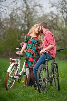 Casal com bicicletas, amando no jardim primavera
