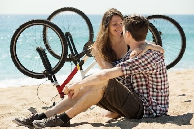 Casal com bicicletas na praia