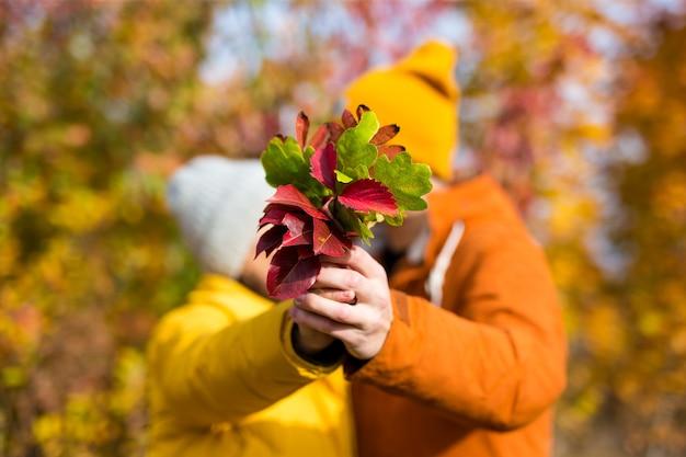 Casal com buquê de folhas de outono se beijando na floresta ou parque de outono