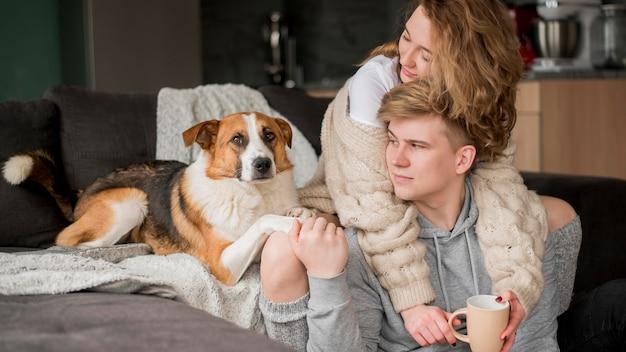 Casal com cachorro abraçando