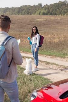 Casal com cachorro e carro ao ar livre