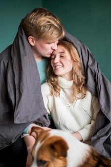 Casal com cachorro e cobertor