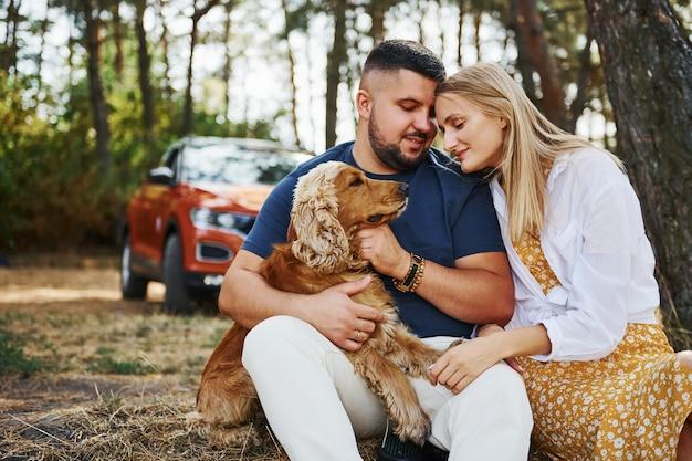 Casal com cachorro tem fim de semana ao ar livre na floresta com o carro atrás deles.