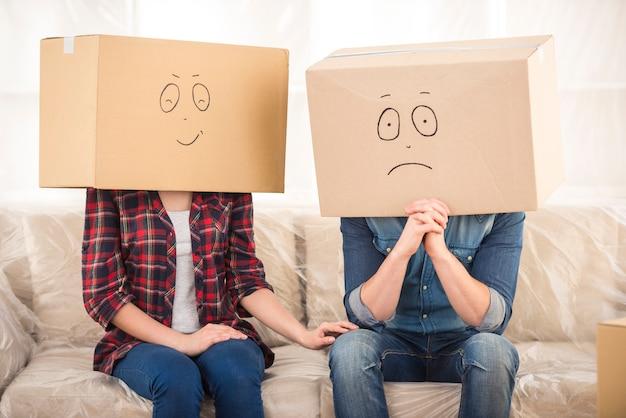 Casal com caixas de papelão na cabeça.
