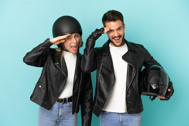 Casal com capacete de motociclista sobre fundo azul isolado acaba de perceber algo e tem a intenção de encontrar a solução