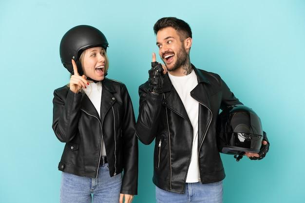 Casal com capacete de motociclista sobre fundo azul isolado com a intenção de perceber a solução enquanto levanta um dedo