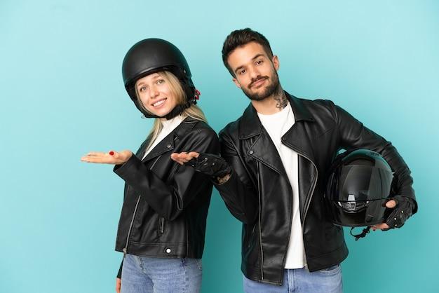 Casal com capacete de motociclista sobre fundo azul isolado estendendo as mãos para o lado para convidar para vir