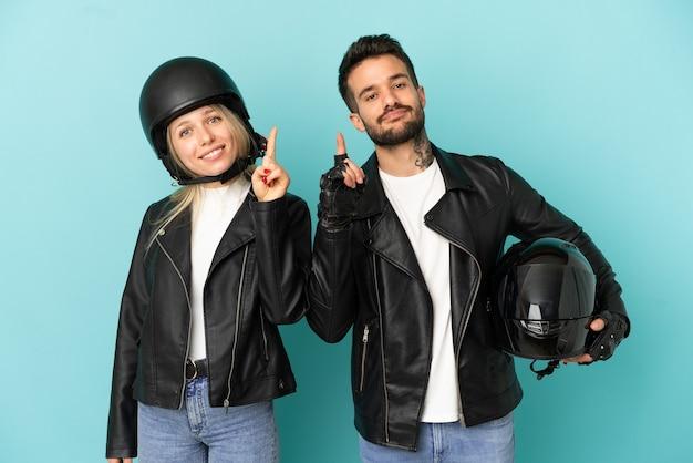 Casal com capacete de motociclista sobre fundo azul isolado mostrando e levantando um dedo em sinal dos melhores