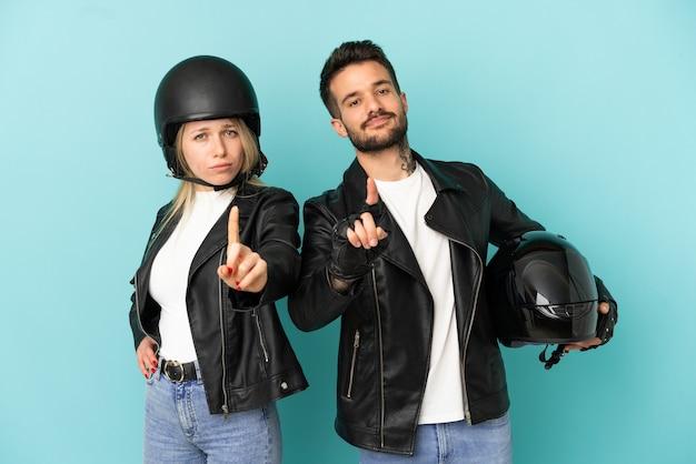 Casal com capacete de motociclista sobre fundo azul isolado, mostrando e levantando um dedo