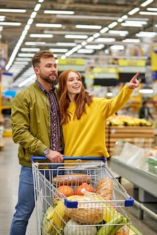 Casal com carrinho de compras comprando comida em mercearia ou supermercado, mulher aponta o dedo para o lado, pede ao marido para comprar algo
